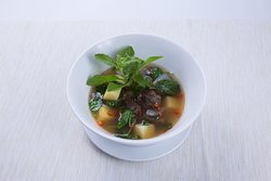 Authentic recipe Thai soup with stewed beef, potatoes, chili and basil