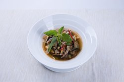 Spicy Thai soup with minced sea bass and local herbs and spices