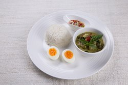 Green chicken curry with coconut shoots served with a boiled egg and steamed rice