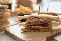 Club sandwich with egg, ham, lettuce and tomato served with fries