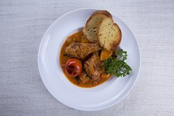 Chicken stew with carrots, potatoes and tomatoes served with bread and fries