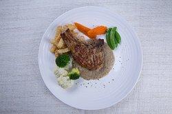 Grilled pork chop steak served with mushroom cream sauce and steamed vegetables