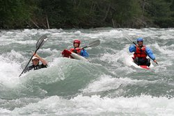 Guests whitewater kayaking with instructor
