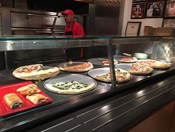 The whole variety of pizzas available by the slice.