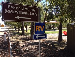 Tourist sign pointing to the RM Williams Monument. On the right is the Memorial Park and playground.