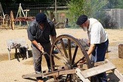 Après avoir été chauffés à blanc dans un foyer circulaire recouvert de mottes de terre, les cercles de fers sont portés sur la roue de bois. Aussitôt refroidis et frappés au marteau par le charron et ses aides.