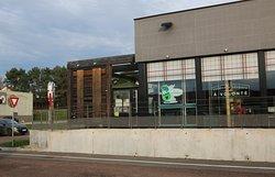La façade du restaurant, il y a un parking pour voitures et un parking abrité pour vélos.