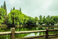 中国安徽省舒城县,飞霞公园.  A pond surrounded by a walking trail and trees at Feixia Park in central Shucheng, Anhui Province, China.