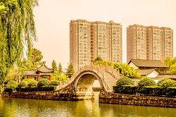 中国安徽省舒城县,飞霞公园.  A walking bridge at Feixia Park in central Shucheng, Anhui Province, China.  Buildings from the surrounding city can be seen in the background.