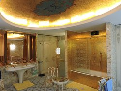 Bagno con soffitto in mosaico d'oro come anche i servizi e mobilio.