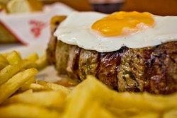 "Bife de Chorizo ""Pippo"".  460 grs. de Bife de Chorizo de Ternera con  huevo frito, morrones asados y papas fritas,"