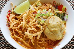 "Y23.""KHAO SOI"" Chieng Mai egg noodle curry ข้าวซอย   Rich creamy yellow curry broth with pickled mustard,  fried shallots, hard boiled farm fresh egg, fried shallots, coconut milk."