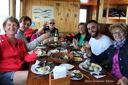 Pasajeros disfrutando de una rica degustación de mariscos, incluida en la navegación.