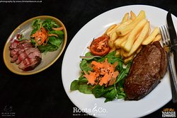 Roots & Co Peppered Steak Strips | With portobello mushroom and blue cheese   8oz Sirloin Steak |  28 days matured 8oz sirloin grilled to your liking and served with grilled tomato, hand cut chips and sauce of choice 20 Post Office Road 01202 558399