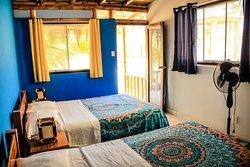 """Bungalow """"Tortuga Marina"""" foto 2- Este bungalow, ubicado en el primer piso,  cuenta con cama doble matrimonial, y una cama de plaza y media. Asimismo, piso de baldosa. El baño privado con buenos acabados. Asimismo, terraza con hamaca y sillón tipo """"perezosa"""". Cuenta con ducha, ventilador, vestidor, accesorios de baño, balcón, Tv LCD 24″  con cable, entrada privada, WIFI gratis en la habitación."""