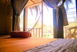"""El bungalow para 6 personas se denomina  """"Estrella de Mar"""" : consta de una cama doble y dos camarotes (4 camas), para una máximo de 6 personas. Asimismo, Tv con cable, ventilador de pie y de pared, agua caliente y frigobar. Baño con buenos acabados. Terraza con vista al jardín, con una hamaca y una silla """"perezosa"""". Foto 8"""