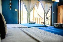 """El bungalow para 8 personas se denomina """" Concha Perla """"  Este bungalow cuenta con dos camarotes y dos camas dobles, para un máximo de ocho personas. Asimismo, Tv por cable, ventilador de pie, agua caliente y frigobar. Baño con buenos acabados. Terraza con vista al jardín, con una hamaca y una silla """"perezosa"""". Posibilidad de una cama extra. Foto 10"""