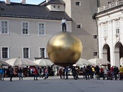 巨大な球体に乗った人物像