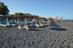 Pláž Kamari s tmavými oblázky