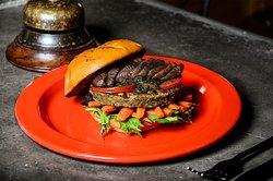 V-Burger $19.9 Balanceada en mezcla de lentejas, quinua y setas, servida sobre pan artesanal vegano, acompañada de crujientes zanahorias, rúgula fresca y portobello con pesto.