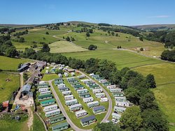 The static caravan park with the farm buildings to the left including reception, shop and cafe. Middlesmoor and Upper Nidderdale as a backdrop.
