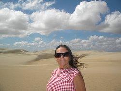 Céu azul, nuvens brancas e areia cor-de-rosa
