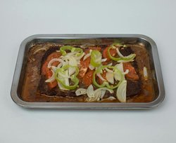 Meat prepared in the oven with onions, peppers and slice of tomatoes.