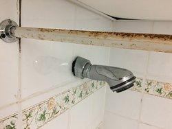Verrostete Duschstange und verdreckte Fliesenfugen (Schimmel?)