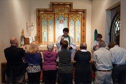 Members of congregation receiving Eucharist in side chapel