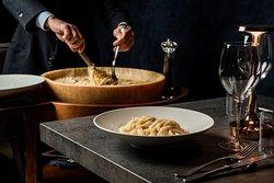 fettuccine all'alfredo, mantecate in forma di parmigiano reggiano