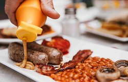 The Full English - Two pork sausages, two rashers of bacon, baked beans, mushrooms, sautéed potatoes, grilled tomatoes, buttered toast, and an egg style of your choice