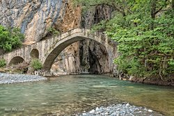 The amazing Portitsa Canyon, having an old stone bridge at its entrance. Ready to explore this magnificent scenery?  #greek_adventure #greece #portitsa #canyoning #hiking #grevena #experiencedifferentgreece #holidaysingreece