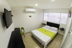 Habitación doble, consta de cama  medidas 1.40m totalmente cómoda, lencería  blanca, escritorio para realizar sus actividades laborales, mueble auxiliar para guardar sus objetos personales. Acondicionadas con aire acondicionado o ventilador.