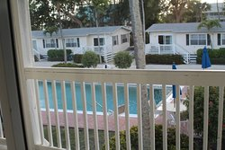 """View from our 2nd floor, partial gulf view room w/2 queen beds.  Railing obstructs view when you sit on balcony.  Across from us are the more expensive """"cottages"""" that reminded us of trailers.  Full disclosure, you CAN see the gulf from this balcony, just not from this angle."""