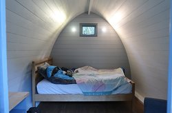 Inside the furnished family pod at Cwmcarn forest - has a double bed, chair and small kitchenette