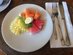 A fruit plate and a glass of juice is served with every breakfast
