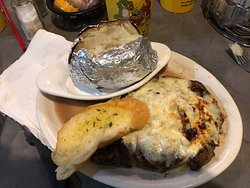 Rib-eye steak topped with cheese and crab