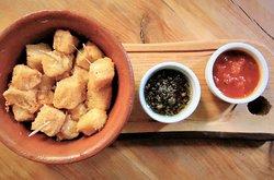 Cubos de muzzarella apanados con salsa fileto y pesto.