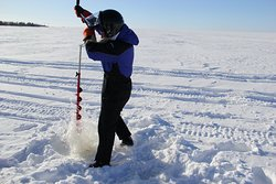 Drilling a hole for ice fishing on Gulf of Bothnia