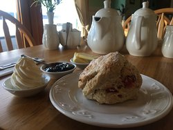 Freshly baked cherry scone with butter homemade jam and cream.