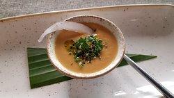 Crema de apio con leche de coco, lemongrass y aceite de chile, con una lámina de coco fresco