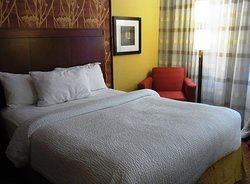 One of the two beds, comfortable arm chair and lamp