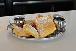 Beignets lightly fried dough rolled in cinnamon sugar glaze and topped with powdered sugar