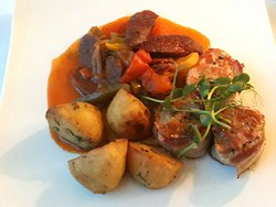 Bacon wrapped pork medallions with sausage and vegetable stew and roast potatoes