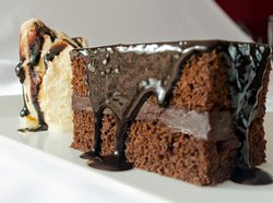 Chocolate cake covered with a rich, moist, chocolate ganache. Served with a scoop of homemade vanilla ice cream and topped with chocolate sauce