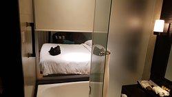 Deluxe Badezimmer Blick durch eine Glaswand von der Dusche aufs Bett mit elektrischem Rollo