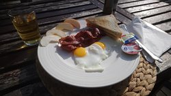 English breakfast- there is a hash brown and a tomato hidden beneath the bacon