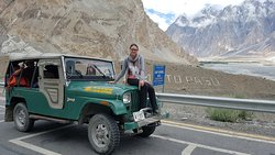 A foreign tourist with a Willys 72 Jeep at Passu