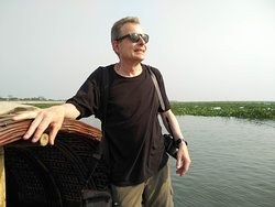 A senior solo traveler is in boat on Meghna River.
