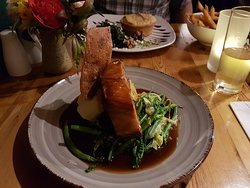 Belly pork with mashed potato, french beans and spring cabbage Butternut Squash and feta tart in the background